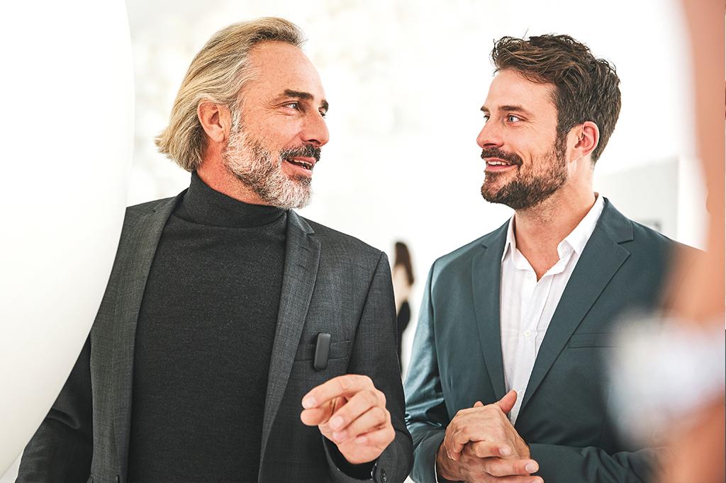 Älterer und jüngerer Mann im Berufsalltag.