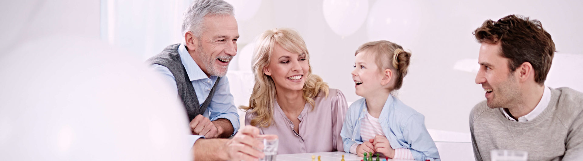 Mother, father, child and grandfather sit around the table at home. They play a board game together and laugh.