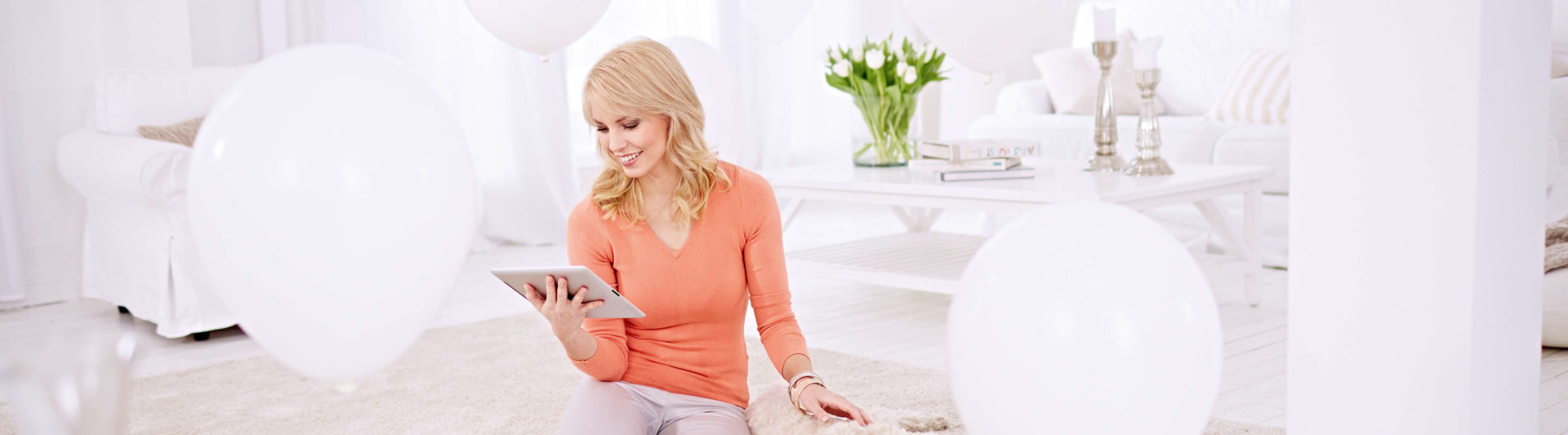A woman sits on the carpet in the living room and holds a tablet computer in her hands. She reads happily on her tablet.
