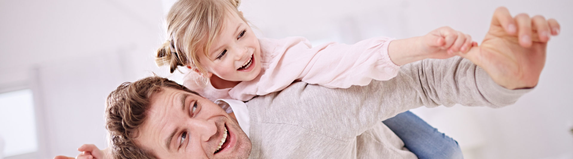 A father carries his small daughter on his back through the living room with his arms spread out wide.