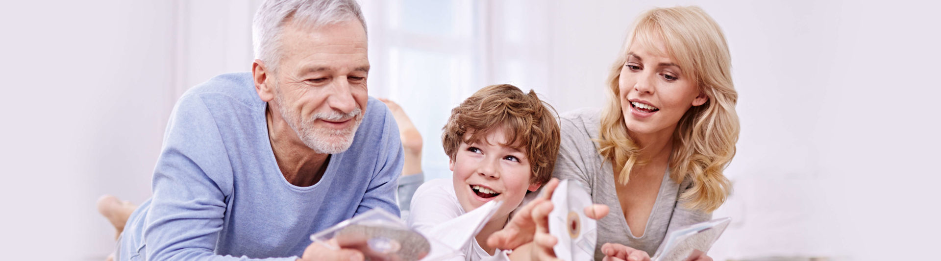 Grandfather, daughter and grandchild lie on the floor, hold CDs in their hands and listen to music.